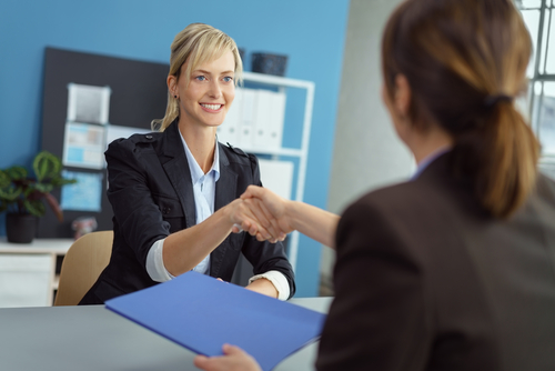 New female graduate shakes hands across desk with employer at close of successful school-based therapy job interview.