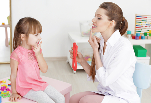 "Female speech language pathologist (SLP) holds plastic letter ""S"" and points to lips, working with girl on articulation goal."