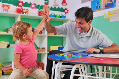"""Smiling male physical therapist in school setting gives kindergarten girl """"high five"""" after she completes a block puzzle."""