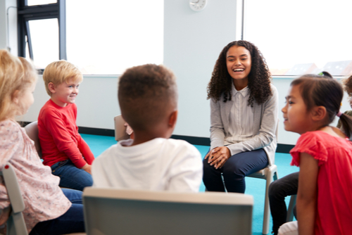 New female school-based therapist sits in circle with five elementary school boys and girls during group session.