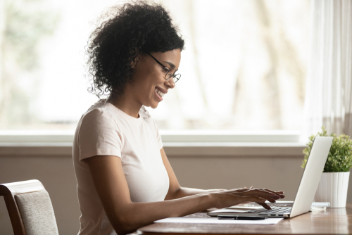 Recently graduated woman sits at desk in sunlit apartment writing her entry-level therapy resume on her laptop computer.