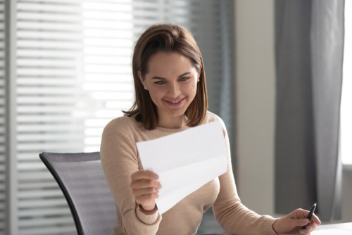 Female related services staffing agency hiring manager smiles as she sits and reviews a one-page entry-level therapy resume.