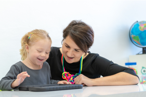 Female school-based occupational therapist kneels next to girl with Down syndrome using tablet computer.