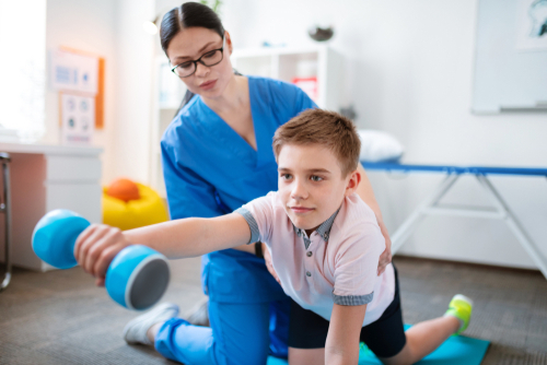 Female school-based physical therapist holds male student by waist as he kneels on mat and holds a dumbbell in his right hand.