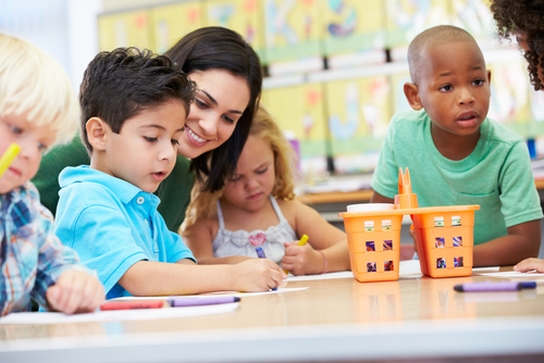 Female school-based therapist sits at classroom table where elementary students practice pencil grip in occupational therapy.