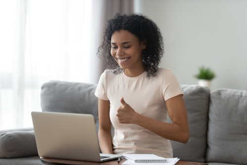 """Female school-based therapist sits at laptop giving """"thumbs up"""" to student via FERPA- and HIPAA-compliant teletherapy platform."""