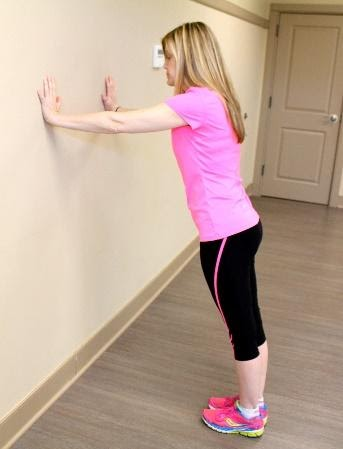 Young middle school girl performs pushups against a wall at home as a movement break in her online learning session.