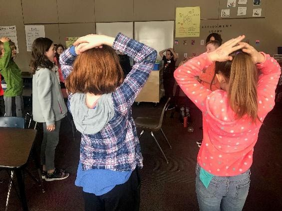 Older elementary school students in classroom gently press their hands on top of their head for proprioceptive sensory input.