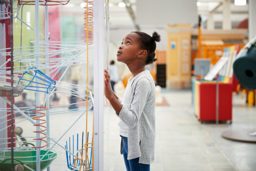 Young elementary school girl touches display case while admiring an exhibit on a field trip for children with Autism.