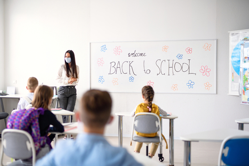 """Female teacher stands at front of classroom where students sit at desks six feet apart, whiteboard reads """"Welcome Back to School."""""""