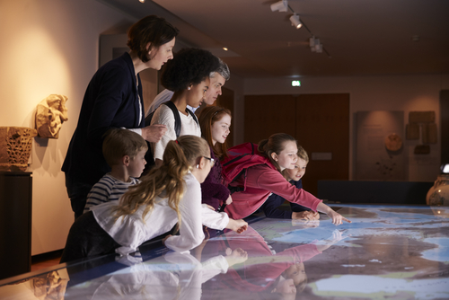Group of school children with Autism and SPD on field trip in museum look at large, illuminated map, supervised by teachers.