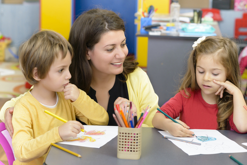 Female school-based occupational therapist kneels between elementary school boy and girl drawing with colored pencils at table.