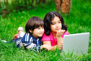 Schoolboy and girl lie on stomachs in grass, using laptop for extended school year (ESY) programming.