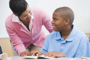 Female middle school teacher leans over to support male student with autism in the classroom as he reads a book aloud.