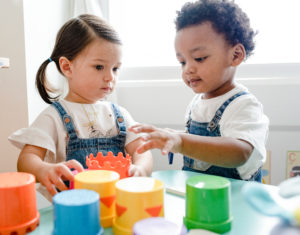 Girl and boy in child care center stand at low table playing with plastic cylinders as part of early intervention services.