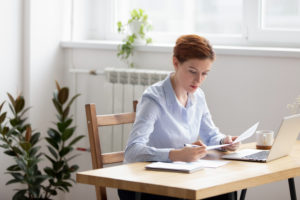 Female special education administrator sits at home with laptop computer, reviewing paper data report about her program.
