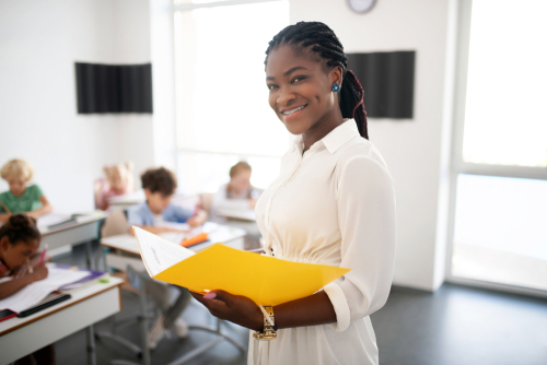 Female special education administrator stands in class where students work holding folder related services in her school.