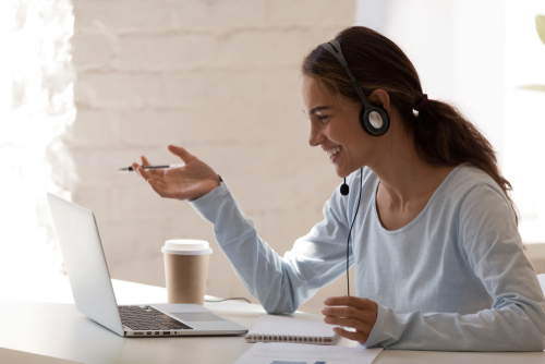 Female school-based therapist wears headset and sits at laptop computer to share teletherapy ideas with her colleagues.