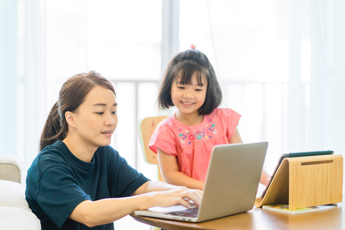 Female school-based therapist working from home on laptop computer while her young daughter, also using a computer, looks on.