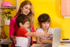 Mother stands behind her young daughter and son to guide them through session with Registered Behavior Technician (RBT).