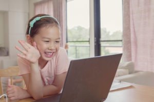 Smiling young elementary school girl sits at desk at home and waves at laptop as her pediatric teletherapy session begins.