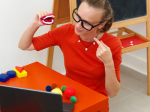 Female school-based speech language pathologist holds and points to model teeth while conducting pediatric teletherapy session.