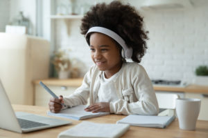 Elementary school girl sits at laptop wearing headphones, practicing handwriting in extended school year (ESY) session.