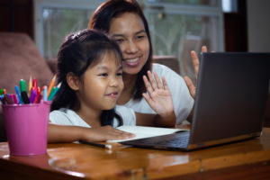 Elementary school girl and her mother wave to Registered Behavior Technician (RBT) on laptop screen during remote learning.