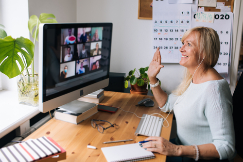 Female school-based therapist waves at teachers and paraprofessionals on computer screen.