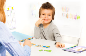 Preschool boy sits at low table in pediatric occupational therapist's room, receiving early intervention services.