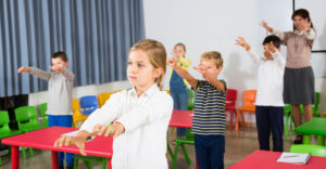Female teacher stands behind students in classroom, leading them in stretch as a Tier 1 physical therapy intervention strategy.