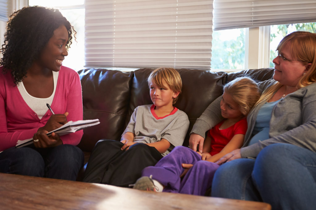 Female school-based social worker making home visit, sitting on couch talking with mother and her elementary age son and daughter.
