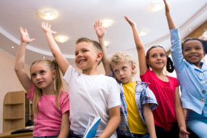 Five elementary school students stretch their right arms toward classroom ceiling during physical therapy Tier 1 intervention.