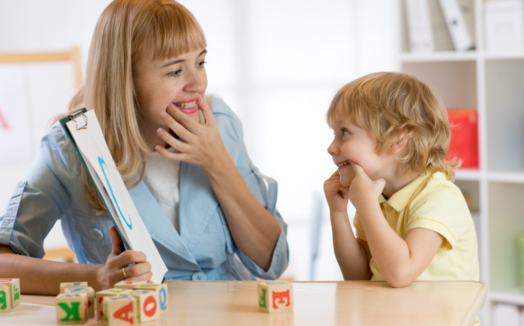 """Female school-based Speech Language Pathologist (SLP) demonstrates mouth position for letter """"C"""" to young male student."""