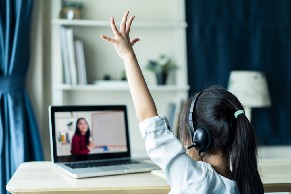 View from behind young girl wearing headphones at laptop, raising hand during special education teletherapy, therapist on screen.