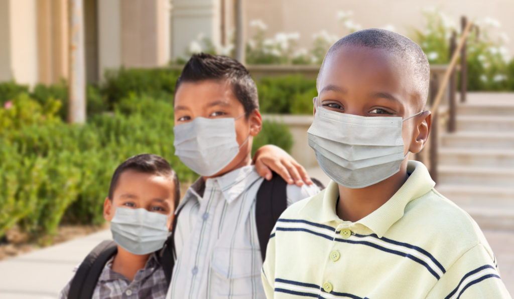 Three elementary school boys outside their school during the coronavirus pandemic, wearing masks over their mouths and noses.