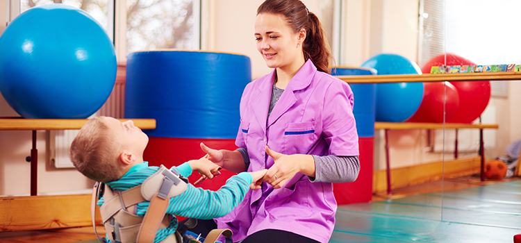 Female school-based physical therapist (PT) kneels on mat with young boy wearing musculoskeletal harness, helping him sit up.