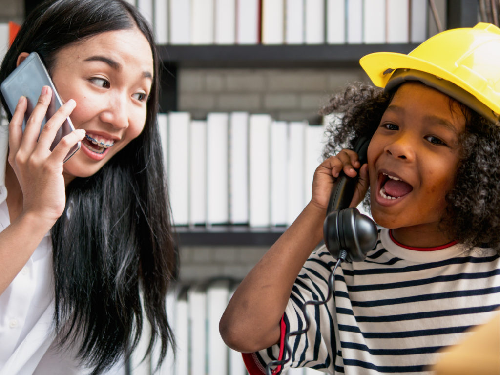Female school-based Certified Occupational Therapy Assistant models talking on phone for young school girl during session.