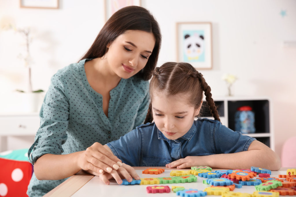 Female school-based Registered Behavior Technician (RBT) helps young girl with autism piece together puzzle pieces during session.