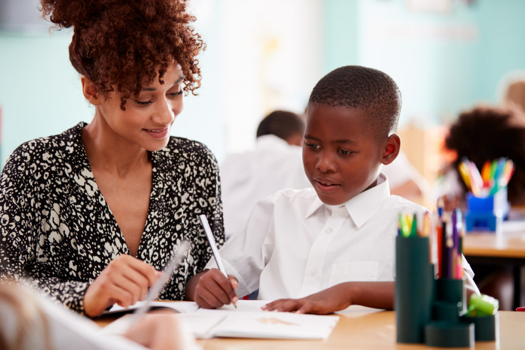 Female school-based Occupational Therapist (OT) sits beside young school boy in classroom practicing his pencil grip.