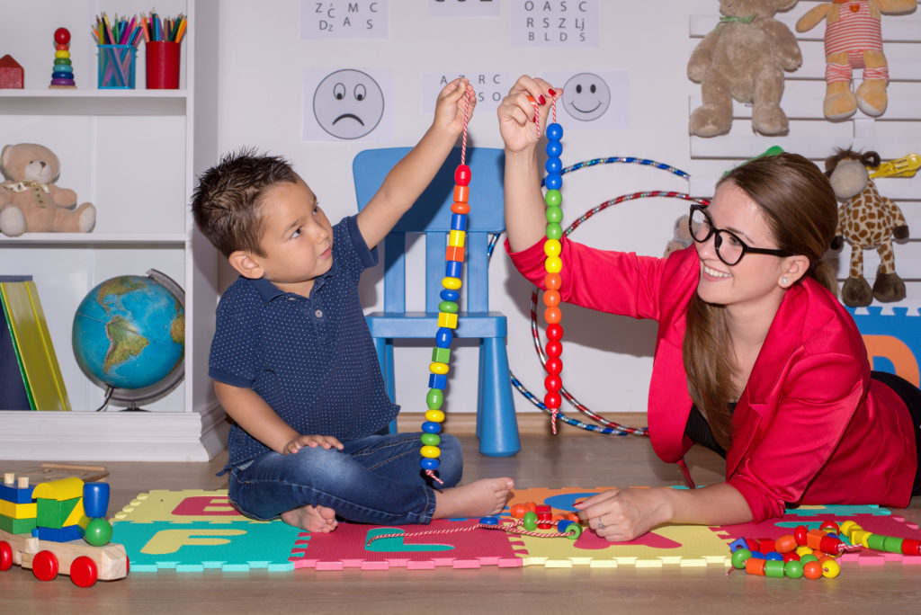 Female school-based physical therapist (PT) lies on stomach to play with string of wooden beads with young cross-legged boy.