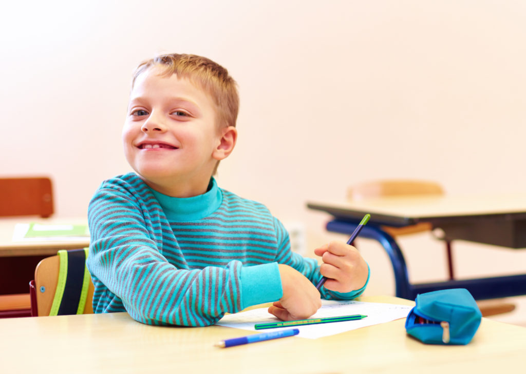 Young elementary school boy sits at desk in classroom practicing handwriting during Applied Behavior Analysis (ABA) therapy.