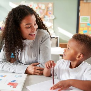 Female school-based occupational therapy expert sits with and smiles at kindergarten boy as he practices his pencil grip.